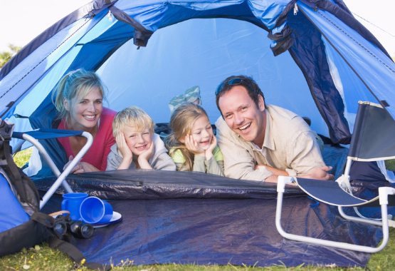family camping in a tent looking out
