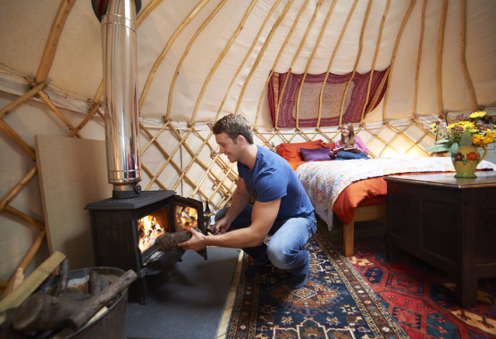 man adds wood to a fire in a luxury yurt