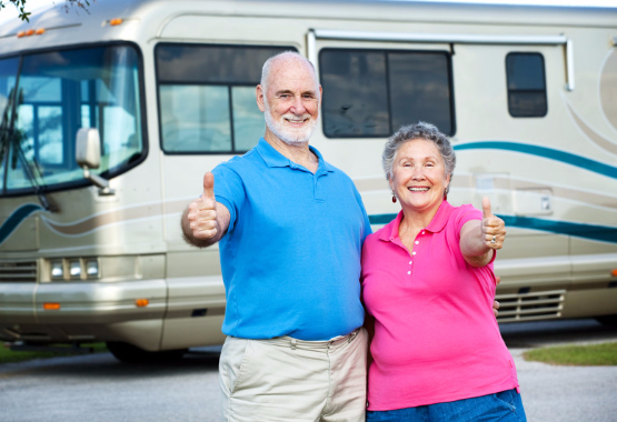 retired couple standing by their recreational vehicle giving a thumbs up