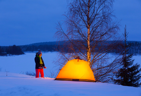 winter camping - woman walks through snow to a glowing tent overlooking a lake
