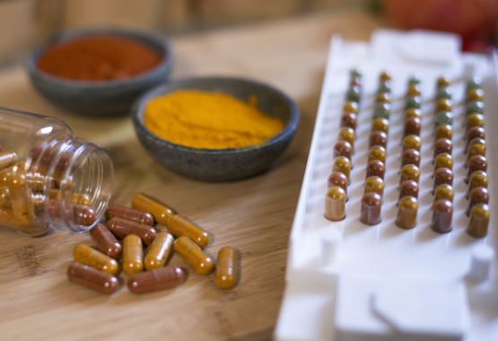CAP-M-QUIK with assortment of filled capsules on wooden board