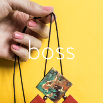 Best Selling Gifts for Bosses | Hand holding Red Resin Necklace on Yellow Background