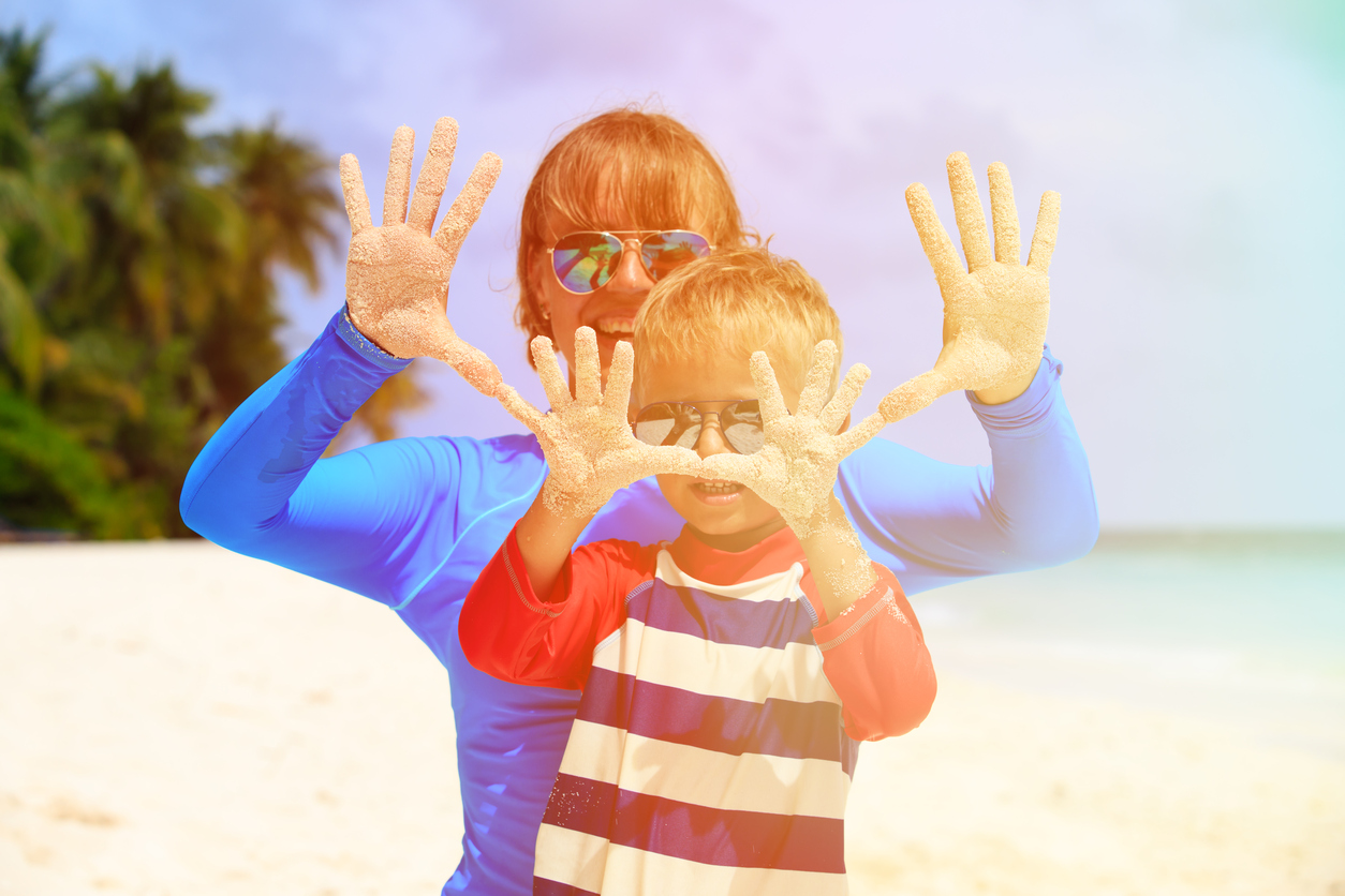 mother & son showing hands facing the sun