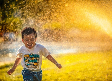 Kid playing in a sprinkler