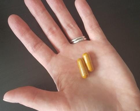 Organic Turmeric Capsules in woman's hand