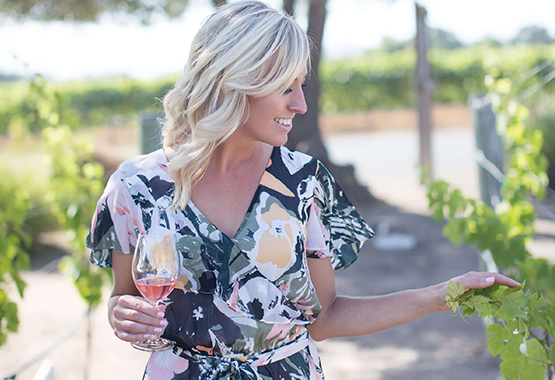Founder Angela Allison drinking CHANCE rosé in a California vineyard