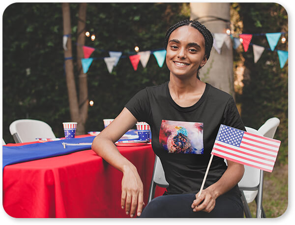 Jazzy Animal Collection Smiling Black Woman Wearing a Tshirt Holding a Small American Flag at a 4th of July BBQ Party Bald Eagle United States